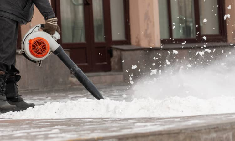 Removing snow from pavement with leaf blower